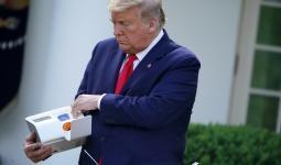 ترامب يمسك بجهاز الاختبار السريع الذي يجرف فحص كورونا في بضع دقائق