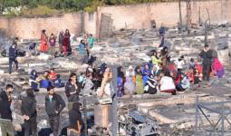 لاجئون سوريون في المخيم بعد إحراقه