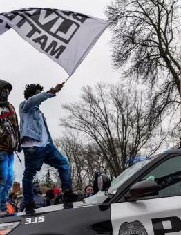 متظاهرون يقفون على سيارة شرطة في بروكلين سنتر