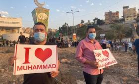 شبان يحملون لافتات نصرة للنبي محمد في ظل الإساءة إليه