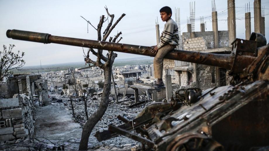 طفل سوري يجلس على دبابة من مخلفات ميليشيات الأسد